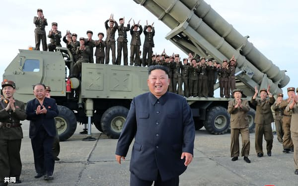 24日、「超大型ロケット砲」の試射を指導する北朝鮮の金正恩委員長(中央)=朝鮮中央通信・共同
