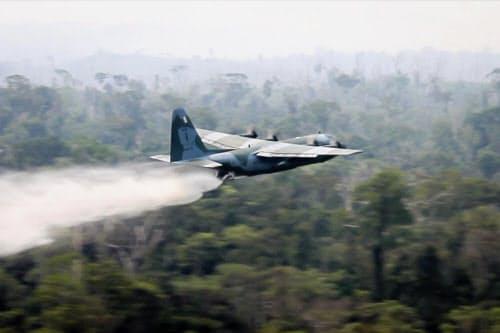 24日、ブラジル北部アマゾン地域の火災で消火活動に当たるC130輸送機=ブラジル国防省提供AP