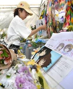 京都アニメーションが制作したアニメのキャラクターを描いた色紙を供える女性(25日午後、京都市伏見区)