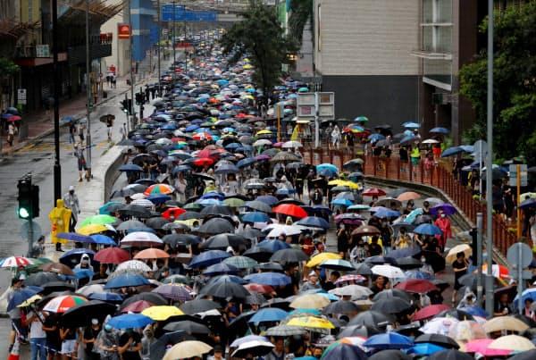 雨の中、多くの人がデモ行進した(25日、香港・葵芳)=ロイター