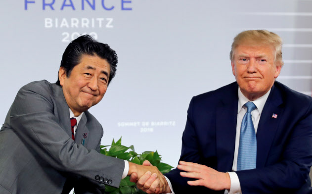 25日、日米首脳会談で握手を交わす安倍首相とトランプ米大統領(フランスのビアリッツ)=ロイター