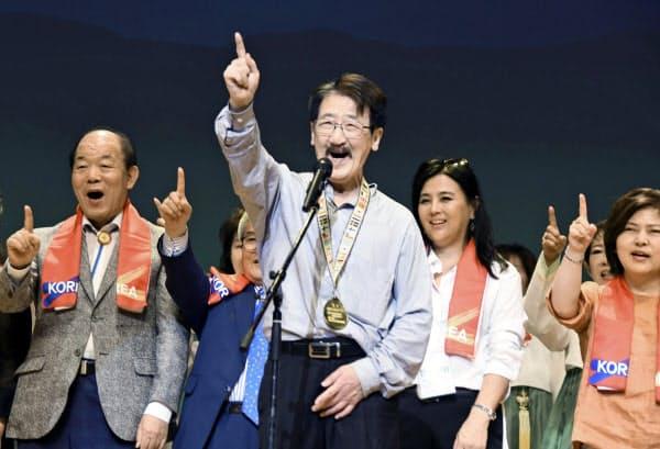 「ワンコリアフェスティバル2019」で、朝鮮語で一つを意味する「ハナ」と呼び掛ける鄭甲寿実行委員長(手前)ら(25日午後、大阪市)=共同