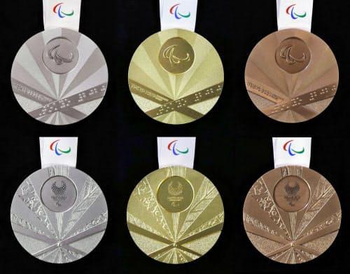 2020年東京パラリンピックの(左から)銀、金、銅の各メダル。「扇」をイメージしたデザインで、表(上列)の扇骨に点字で「TOKYO2020」と表記されている=共同