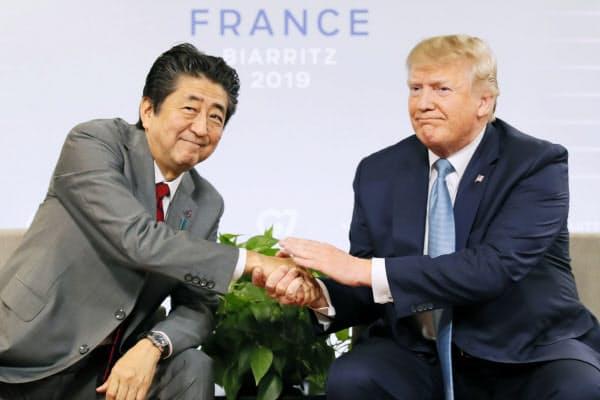 25日、日米首脳会談で握手を交わす安倍首相とトランプ米大統領(ビアリッツ)=共同