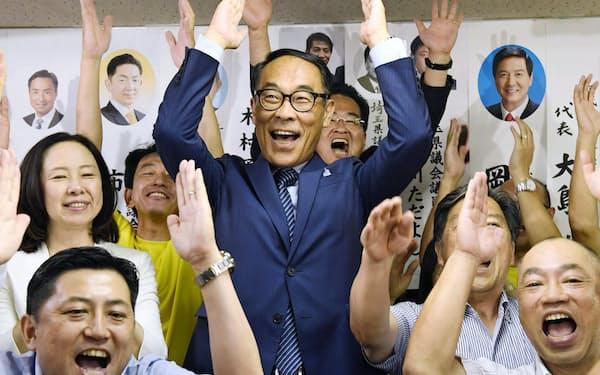 埼玉県知事選で当選が確実となり、支援者らと万歳する大野元裕氏(中央)=25日夜、さいたま市