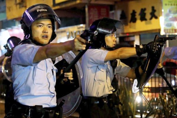 デモ隊に向けて拳銃を構える警察官(25日、香港)=ロイター