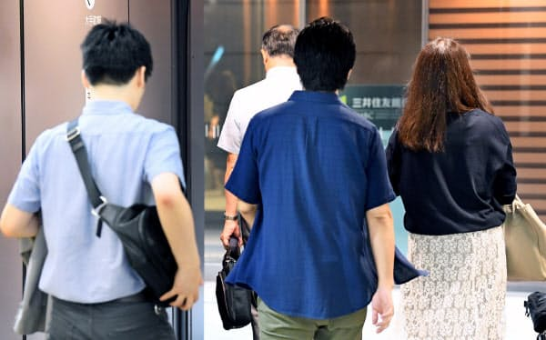 自由な服装で通勤する三井住友銀行の行員ら(7月、東京・丸の内)