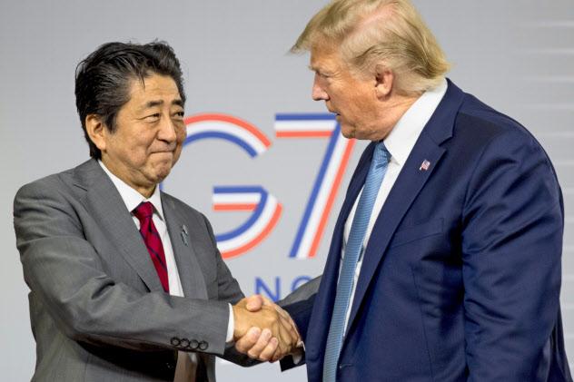 日米は貿易交渉で基本合意した(25日、フランスのビアリッツでトランプ大統領(右)と握手する安倍首相)=AP