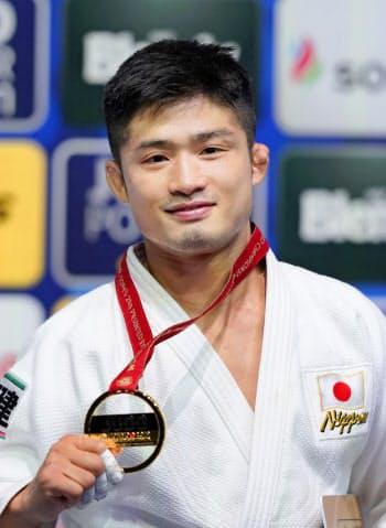 男子66キロ級で初優勝し、金メダルを手に笑顔の丸山城志郎(26日、日本武道館)=共同