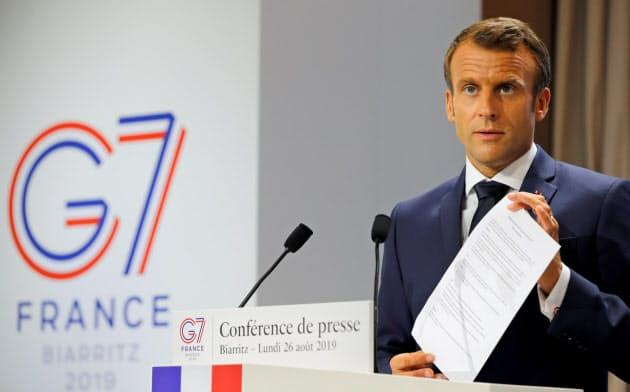 主要7カ国首脳会議(G7サミット)の成果文書を掲げるフランスのマクロン大統領(26日、ビアリッツ)=ロイター