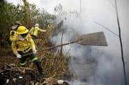 ブラジルのアマゾンの火災現場で働く消防士(26日)=AP