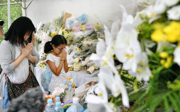 京都アニメーションのスタジオ近くの献花台を訪れ手を合わせる人たち(25日、京都市伏見区)=共同