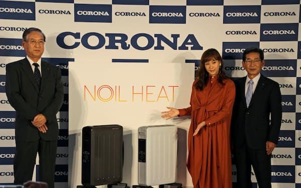 27日、「ノイルヒート」の製品発表会で商品を紹介する小林一芳社長(右)ら(東京都渋谷区)