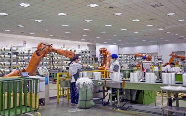 グラスファイバーのロールをロボットの助けを借りて包装する中国・江蘇省の労働者たち。中国の工場では稼働率が低下している=AP