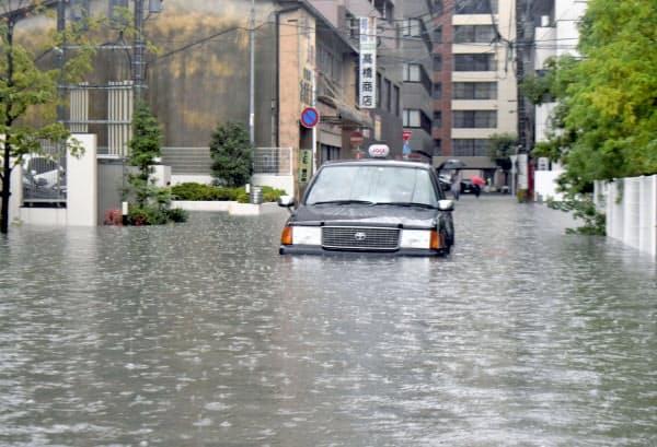 大雨の影響で道路が冠水し、立ち往生したタクシー(28日午前、佐賀市)=共同