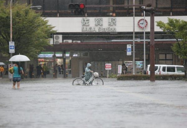大雨で冠水したJR佐賀駅前の大通り(28日午前)=時事