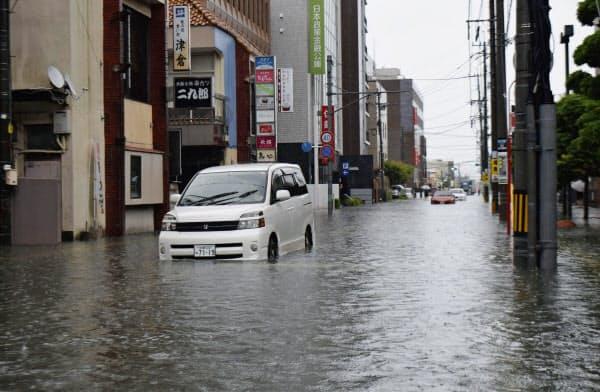 大雨で冠水し、車が立ち往生した佐賀市の道路(28日午前)=共同