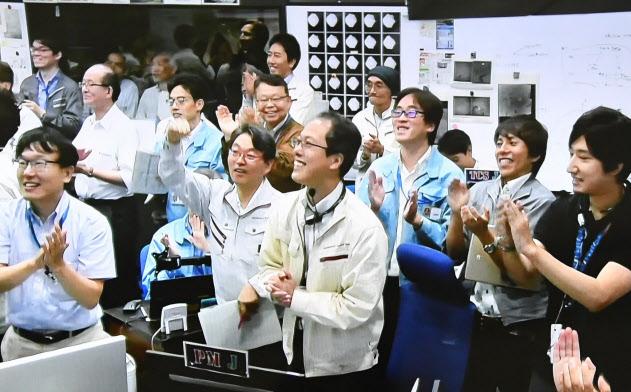 はやぶさ2が小惑星「りゅうぐう」へ着陸し、管制室で拍手する津田雄一プロジェクトマネージャ(中央)=2019年7月11日午前、相模原市(モニター画面より)
