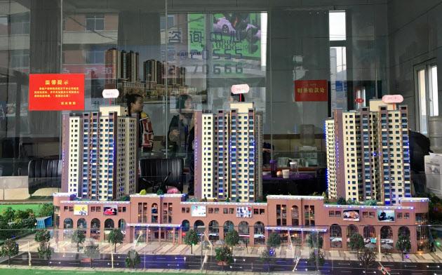 不動産販売の伸び悩みも中国の税収減の一因だ(1月、陝西省で展示された複合ビルの模型)=ロイター
