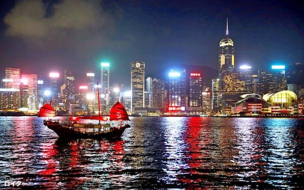 27日、香港の夜景と海に浮かぶジャンク船=ロイター
