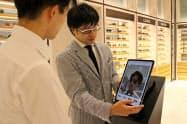 店員がタブレット端末でサングラスのバーチャル試着を案内する(伊勢丹新宿店、東京・新宿)