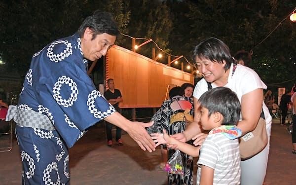 夏祭り会場で家族連れにあいさつする自民党の菅原一秀衆議院議員(左)(東京都練馬区)