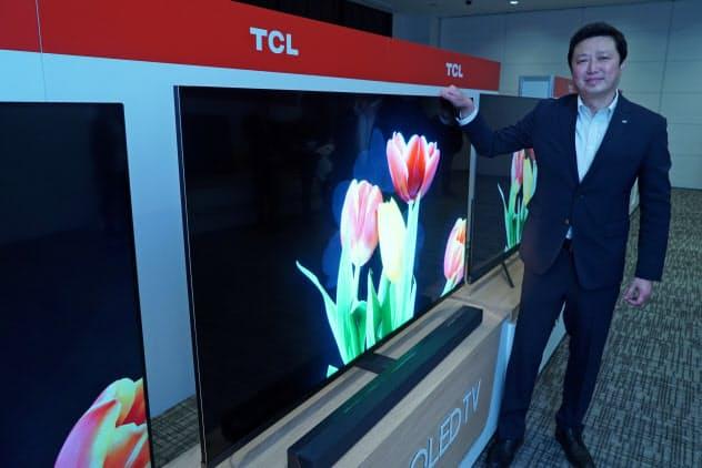 次世代ディスプレー技術「量子ドット」を採用した4K対応テレビ「X10シリーズ」と記念撮影に応じるTCLジャパンエレクトロニクスの李炬代表取締役(29日午後、東京都中央区)