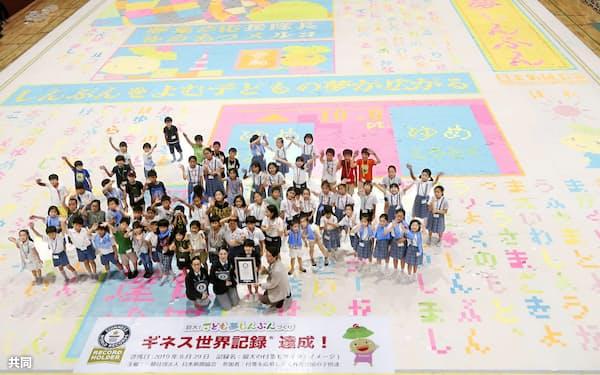 完成した「こども夢しんぶん」の上で手を振る小学生たち=29日、東京都渋谷区
