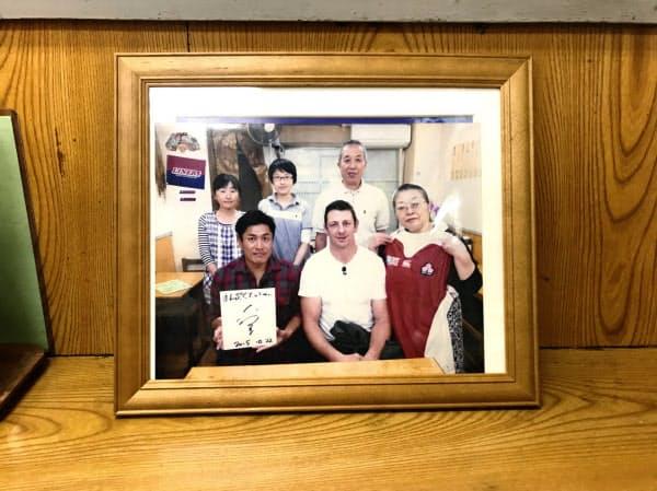 定食店に飾ってある記念写真。前列中央がトンプソン選手(大阪府東大阪市)