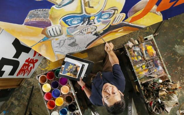 手描きで映画看板を製作する八条祥治さん=小川望撮影