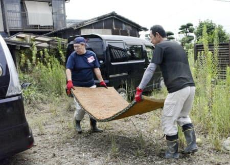 大雨による浸水被害を受けた佐賀県大町町の住宅から畳を運び出すボランティア(31日午前)=共同