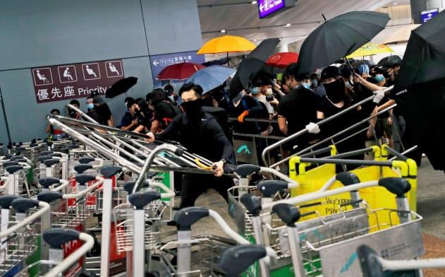 デモ隊が香港国際空港に押しかけ入り口付近をバリケードで封鎖した(1日)=ロイター