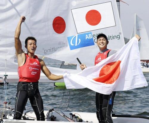 男子470級で銅メダルを獲得し、日の丸を掲げ喜ぶ土居(右)、木村組(1日、江の島ヨットハーバー沖)=共同