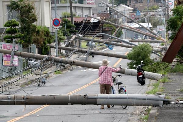 台風の強風で倒れ、道路をふさぐ電柱(2018年9月6日、大阪府泉南市)