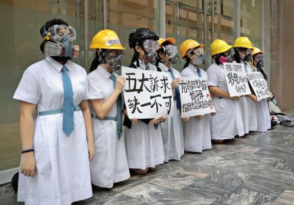 2日、学校でガスマスクとヘルメット姿になり抗議活動する生徒ら=AP