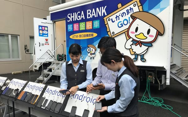 滋賀銀行は2日、移動金融車を使った携帯電話充電サービス提供訓練を実施した(大津市)