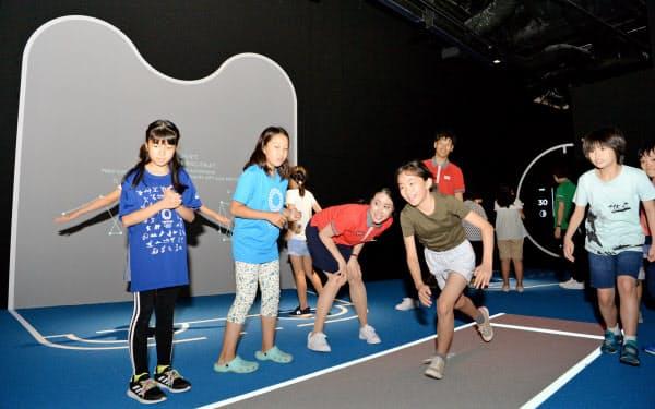 日本オリンピックミュージアムの内覧会で競技を体験する子供たち(2日、東京都新宿区)