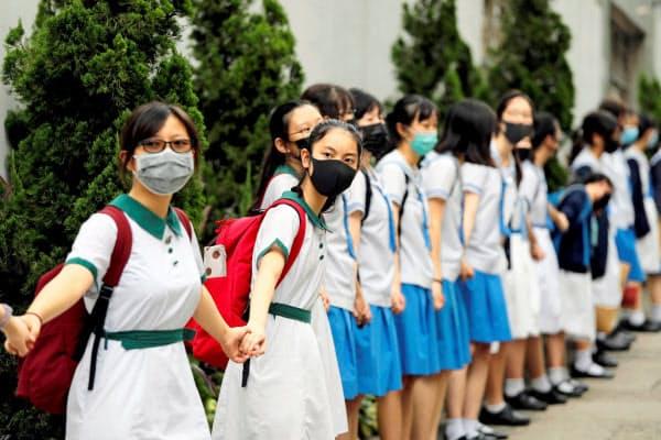 3日、香港で、授業をボイコットして抗議活動に加わる学生ら=ロイター