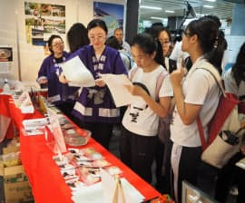 県内大学の留学生が訪日客に製品を紹介する(上毛高原駅)
