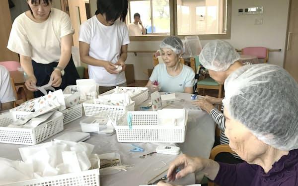 施設スタッフが手伝いながら入居者が作業する(奈良市のリールホーム都祁)