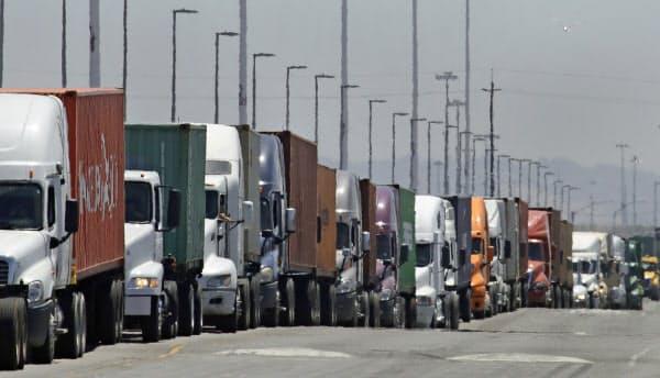 米経済は貿易摩擦や海外経済減速の影響が出ているという(カリフォルニア州の港で並ぶトラックの列)=AP