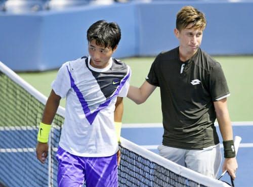 男子シングルス2回戦でアルゼンチン選手(右)に敗れた望月慎太郎(4日、ニューヨーク)=共同