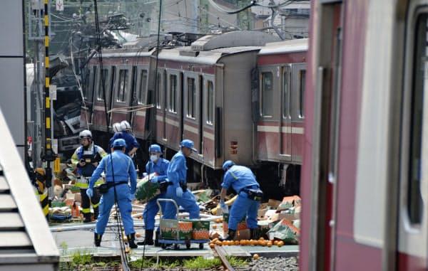京浜急行の車両がトラックと衝突した踏切付近で、散乱したものを片付ける神奈川県警の捜査員ら(5日午後、横浜市神奈川区)=共同