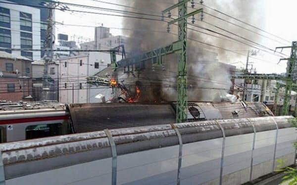 京浜急行の電車とトラックが衝突し、黒煙が上がる事故現場(5日、横浜市神奈川区)=住民提供・共同
