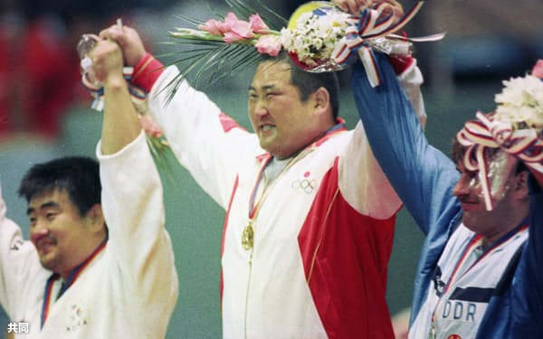 柔道男子95キロ超級で金メダルを獲得し表彰台で声援にこたえる斉藤仁=共同