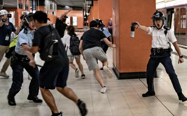 5日、香港の鉄道駅で、催涙スプレーでデモ隊を排除しようとする警官(ゲッティ=共同)