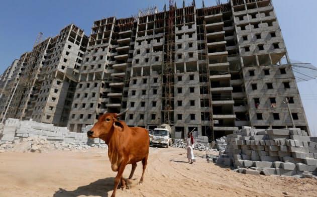 家計引き締めがインド経済を減速させている(西部アーメダバードで建設中の集合住宅)=ロイター