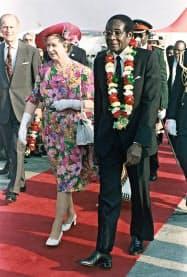 1991年、英国のエリザベス女王(左)を迎える当時のムガベ大統領(ハラレ)=AP