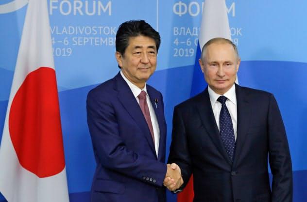 首脳会談は通算27回となった(5日、ウラジオストクでプーチン大統領(右)と握手する安倍首相)=ロイター