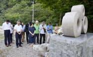 坂本都子さんの慰霊碑で手を合わせる夫堤さんの同僚弁護士ら(7日午後、富山県魚津市)=共同